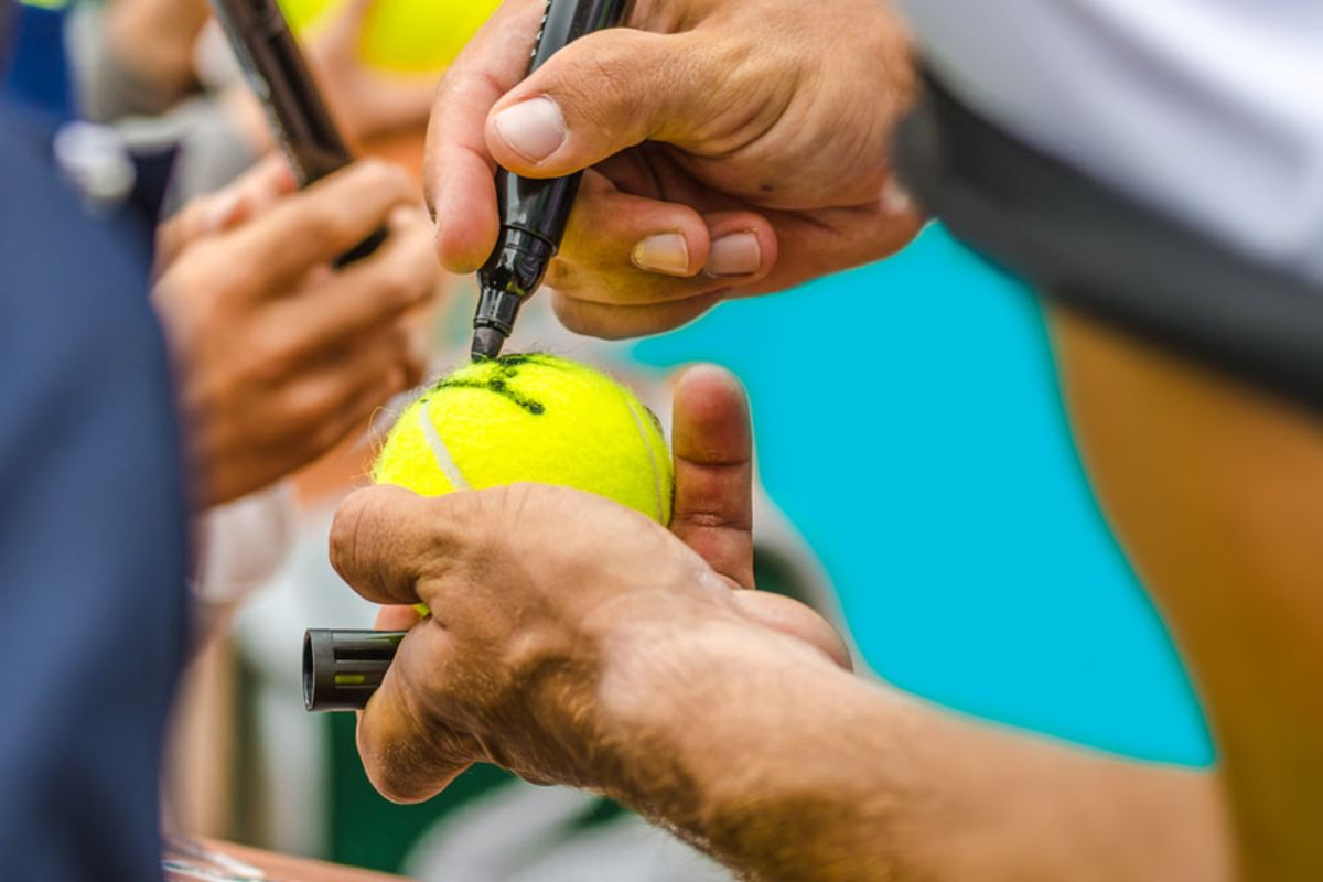 tennis-player-signing-autographs-on-tennis-balls