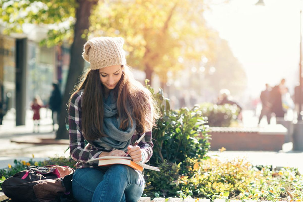 young-female-college-student-reading-book-in-park