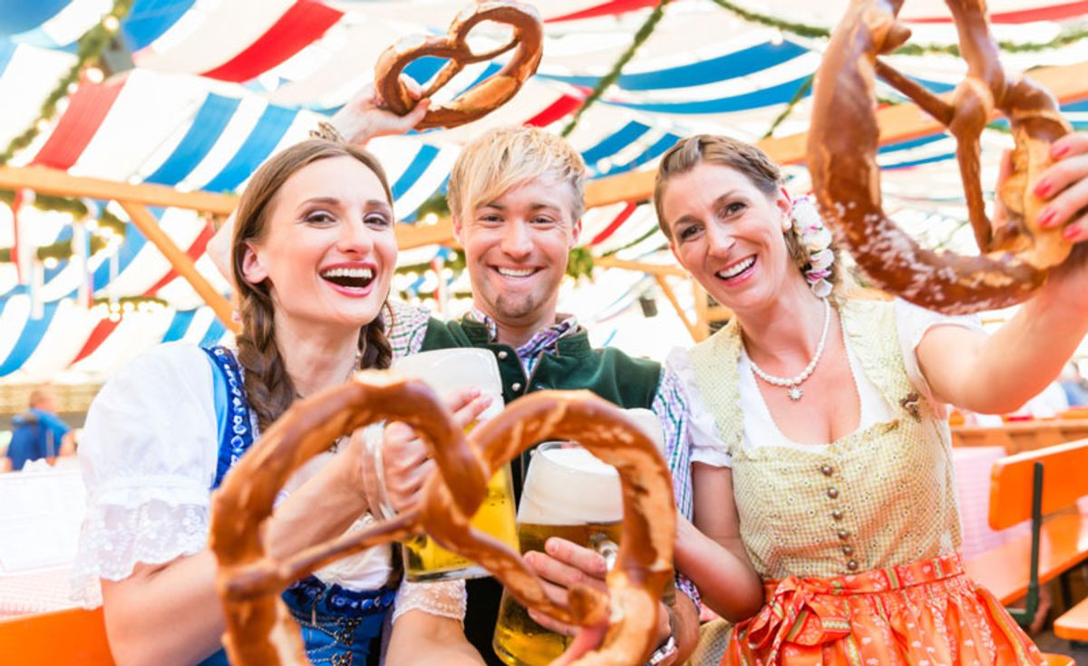 three-friends-in-oktoberfest-costumes-holding-pretzels