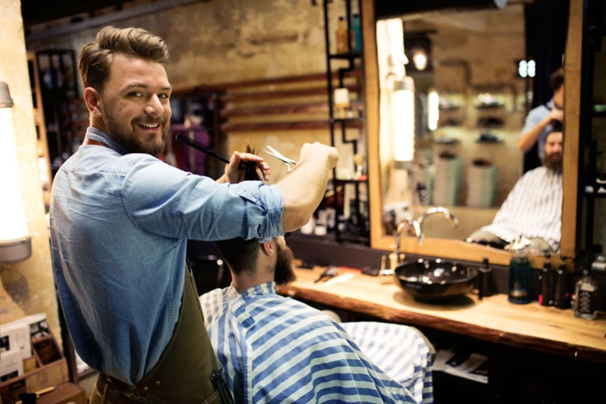 Male hairdresser cutting a man's hair in a grooming salon