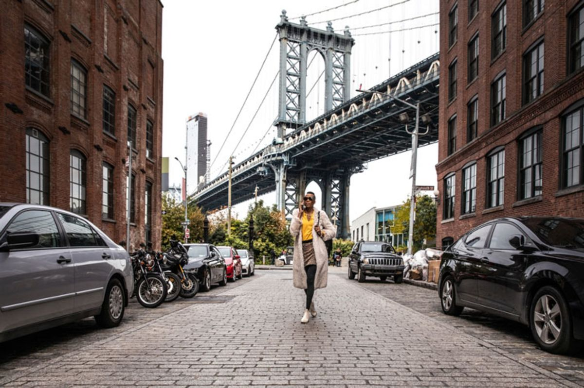 Stylish woman walking in DUMBO with Manhattan Bridge in background