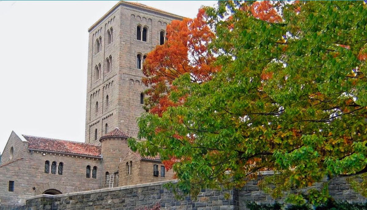 Tower of Cloisters Museum framed by trees in fall colors.