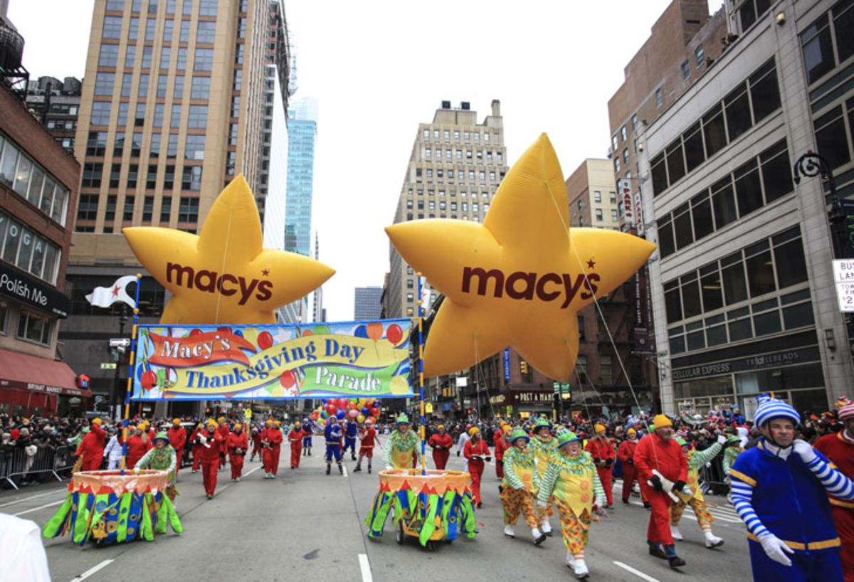 Yellow star Macy's balloons and marchers in Macy's Thanksgiving Day Parade.