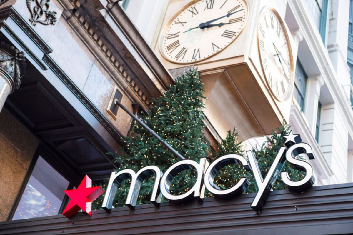 Sign of Macy's with Christmas trees and clock in the background.