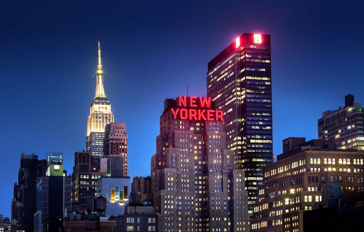 Manhattan skyline with The New Yorker Hotel sign lit at night.