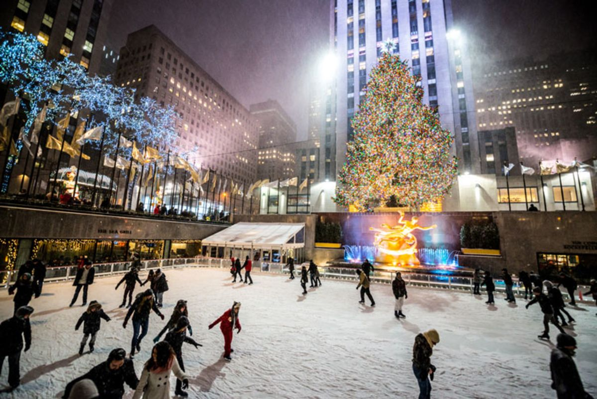 People skating on Rockefeller Center ice rink at night.