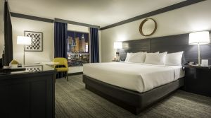 One king bed next to window with view of Vegas Strip