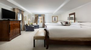 This photo showcases our 450 - 500 square foot room, featuring either two King size or two Queen size beds against the side wall separated by an elegant table with a table lamp, phone and alarm clock. A sitting bench is also situated at the foot of the bed.  Located near the window there are two comfortable armchair with an additional side table and standing lamp. The room also features an armoire, 37 inch flat screen TV and a full stocked mini bar.  The bathroom is made with Italian marble and features a 55 gallon soaking tub.