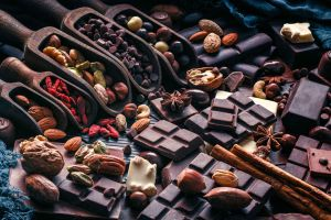 Table with dark chocolate bars, spices and ingredients.