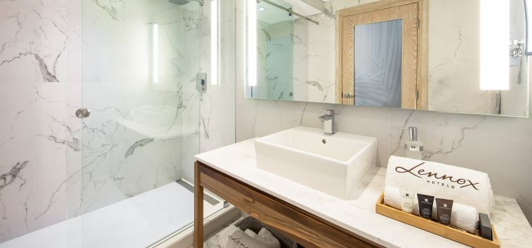 A private bathroom features clean marble on countertops and walls