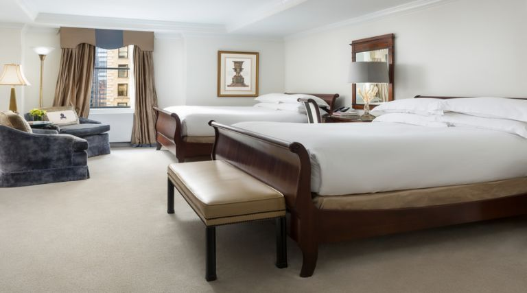 This photo showcases our 495 square foot room, featuring two Queen size bed against the side wall with one night stand between the two beds. Across from the beds there is a seating arrangement which consists of two armchairs and a small table. In addition there is an armoire with dresser drawers and a 43 inch flat screen TV. Next to the armoire you will find a fully stocked mini bar, including wine, bottled beverages and assorted snacks available for purchase. The room also features a full size work desk, an Italian marble bathroom with a 55 gallon soaking tub and a vanity.