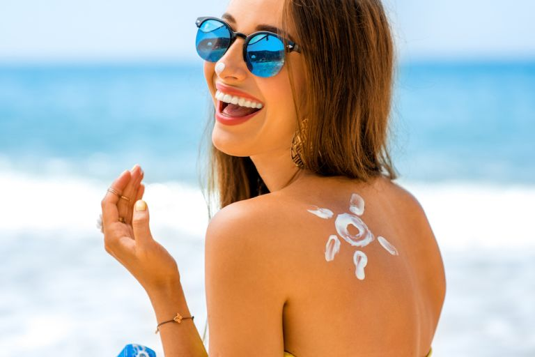 woman-puts-sunscreen-on-miami-beach-weekend