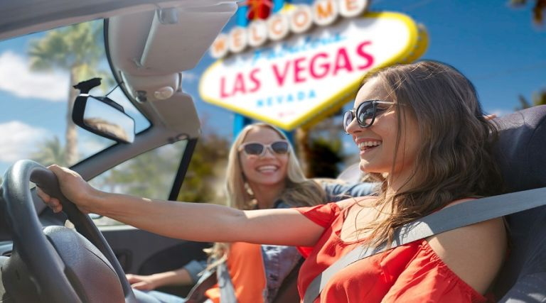 Two women in convertible car with Las Vegas sign. Daytime