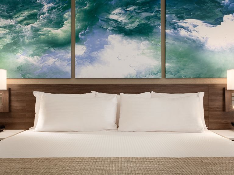 King bed with ocean paintings above headboard