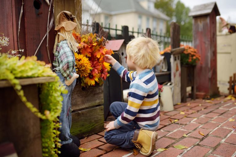 Little boy touching fall scarecrow decoration