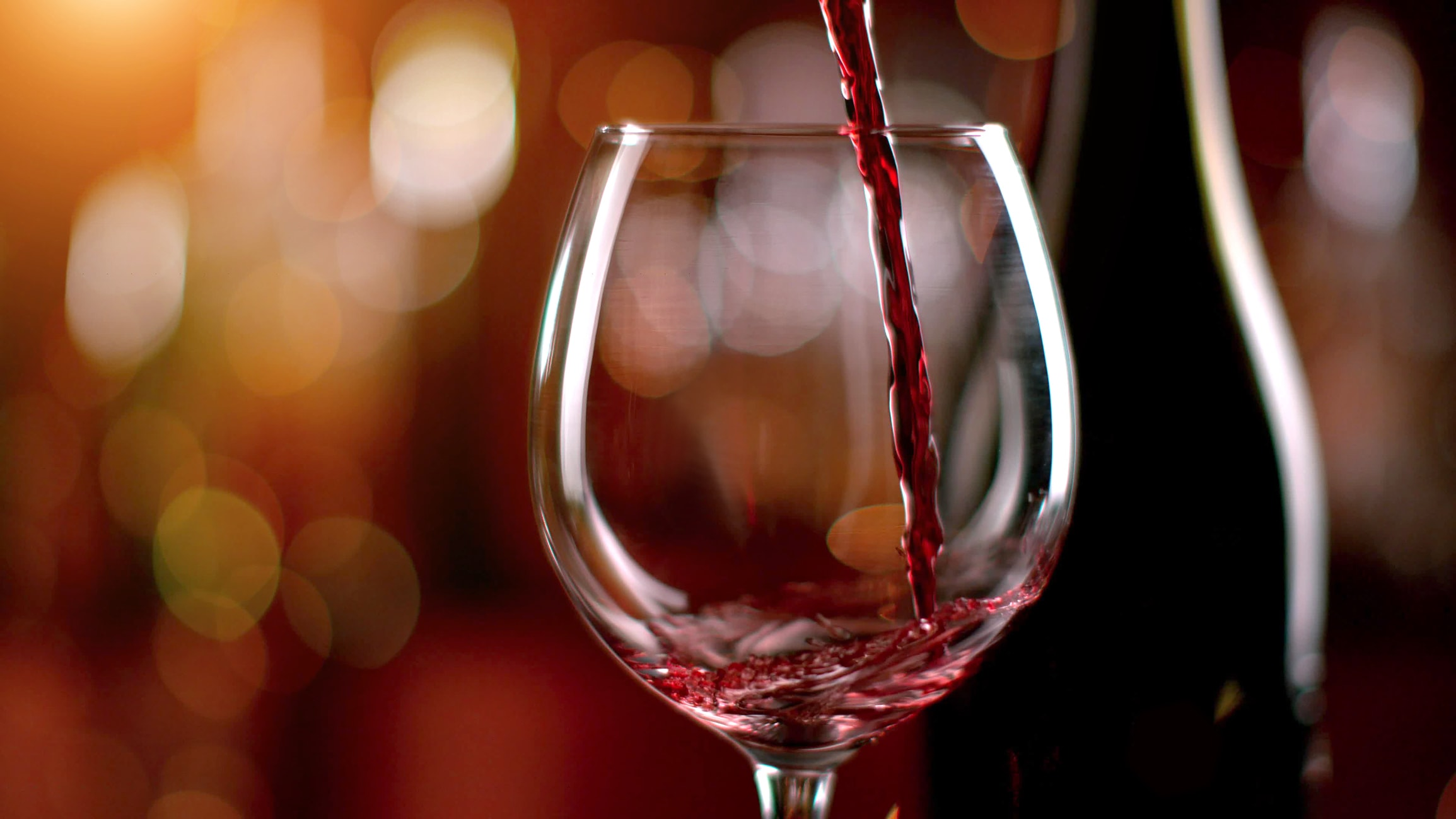 red wine being poured into wine glass with bokeh background