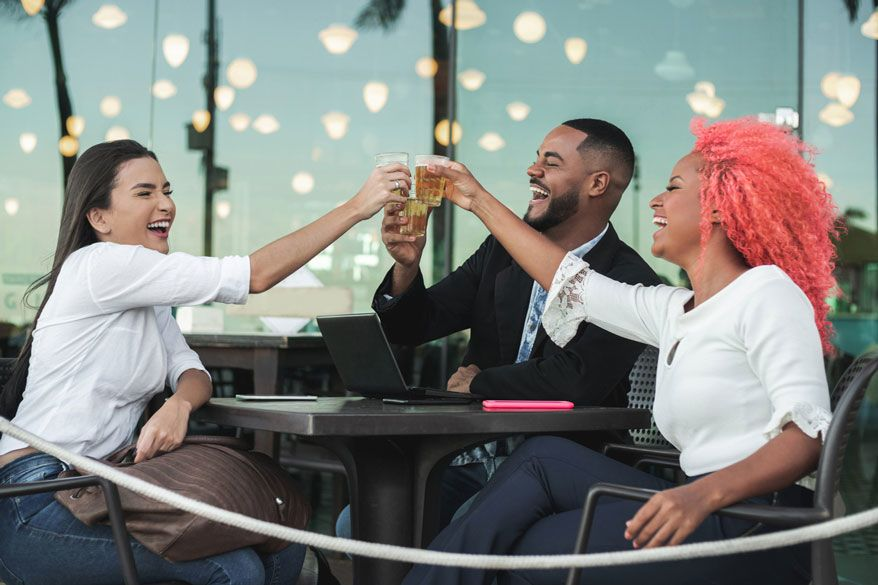 three-office-workers-cheering-in-an-outdoor-bar