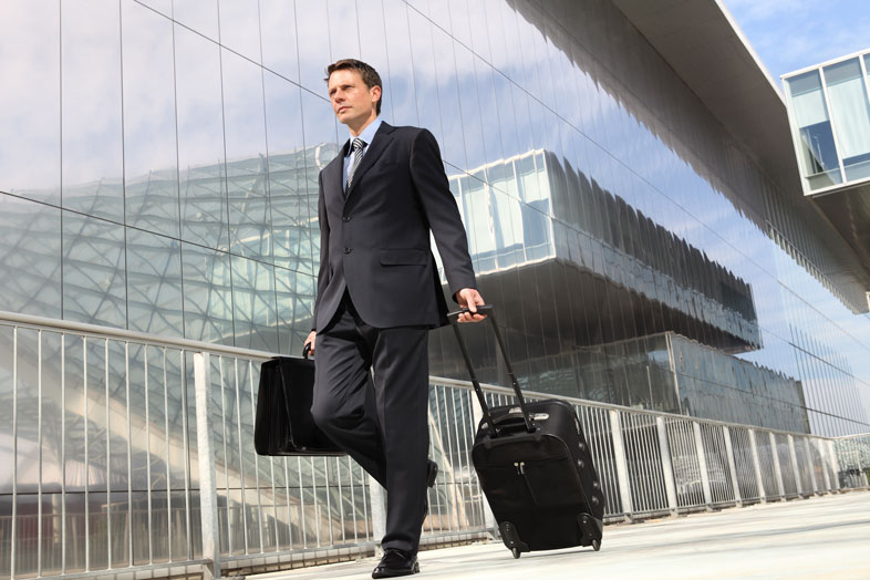 businessman-walking-outside-airport-with-suitcase-and-briefcase