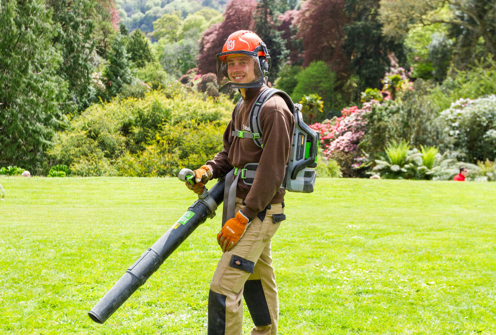 Gardener with electric leaf blower
