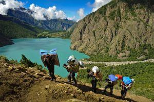 Top Trekking in Nepal | Trekkers hiking along Phoksumdo lake in lower Dolpo, Nepal.