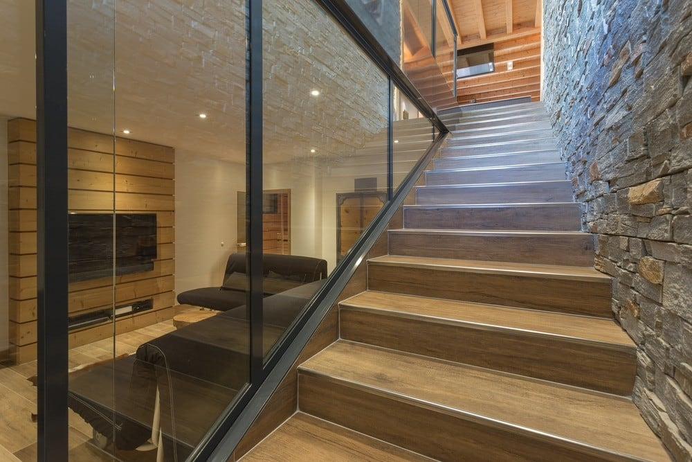 Stone-lined staircase in addition to a mountain home by  Chevallier Architectes