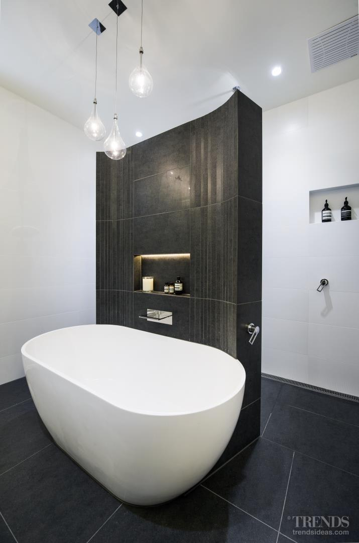 Contemporary bathroom renovation with freestanding tiled wall