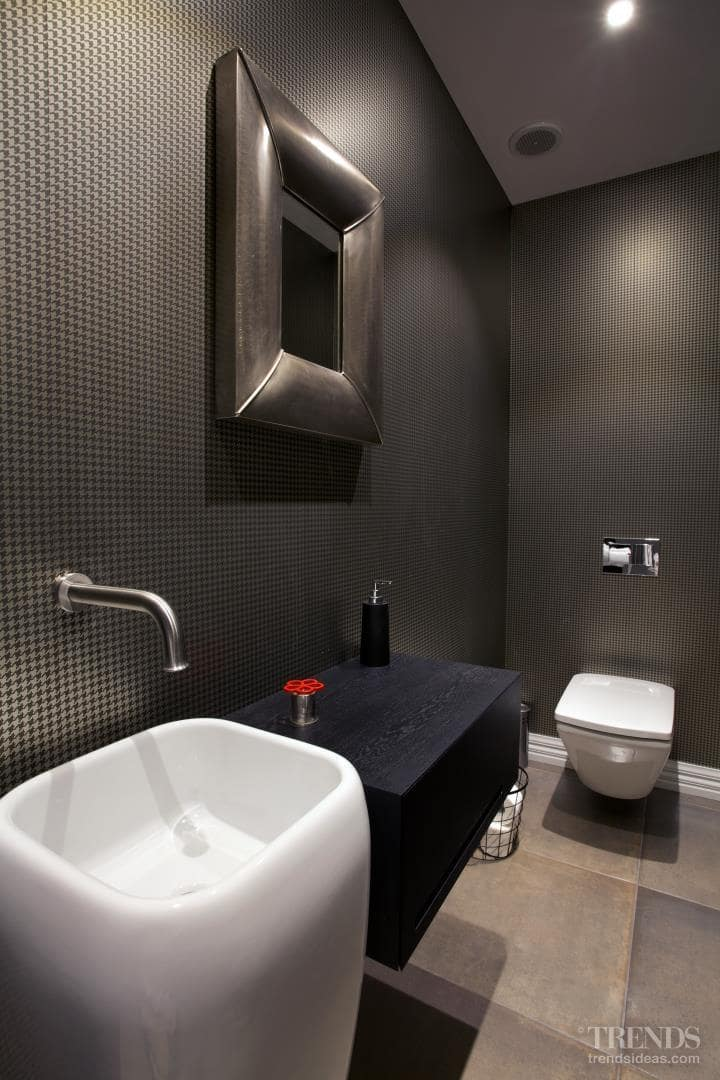 Dark internal powder room with houndstooth wallpaper and moody ambience
