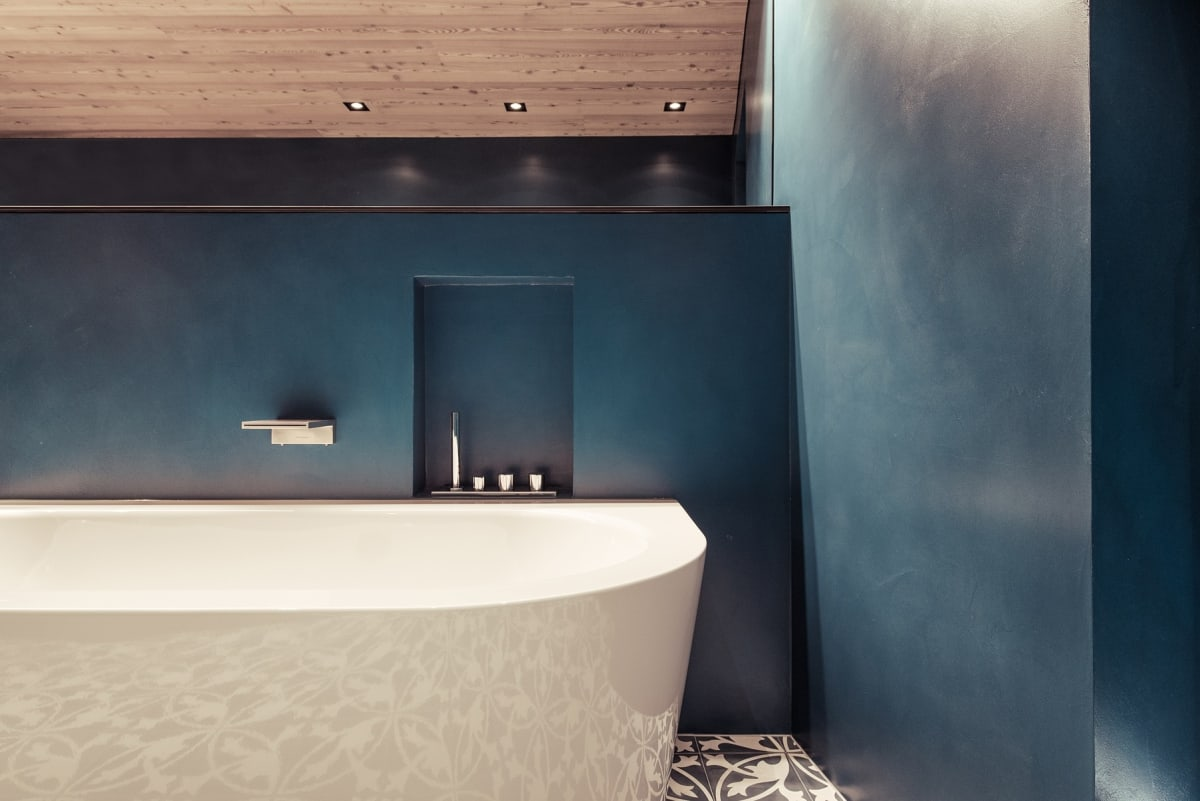 The material use in the bathroom makes for an interesting combination, with a large bathtub, wall-mounted tap, tiled floor and blue walls