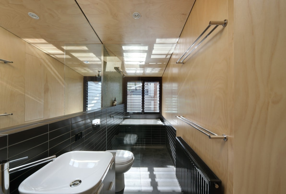 A bathroom of contrasts, this space features black tiles and wood walls