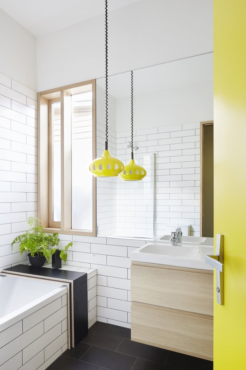 Timber frame windows and white tiles keep the bathroom bright and open