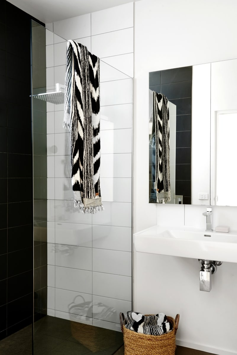 The bathroom features a combination of black and white tiles, with a large glass panel
