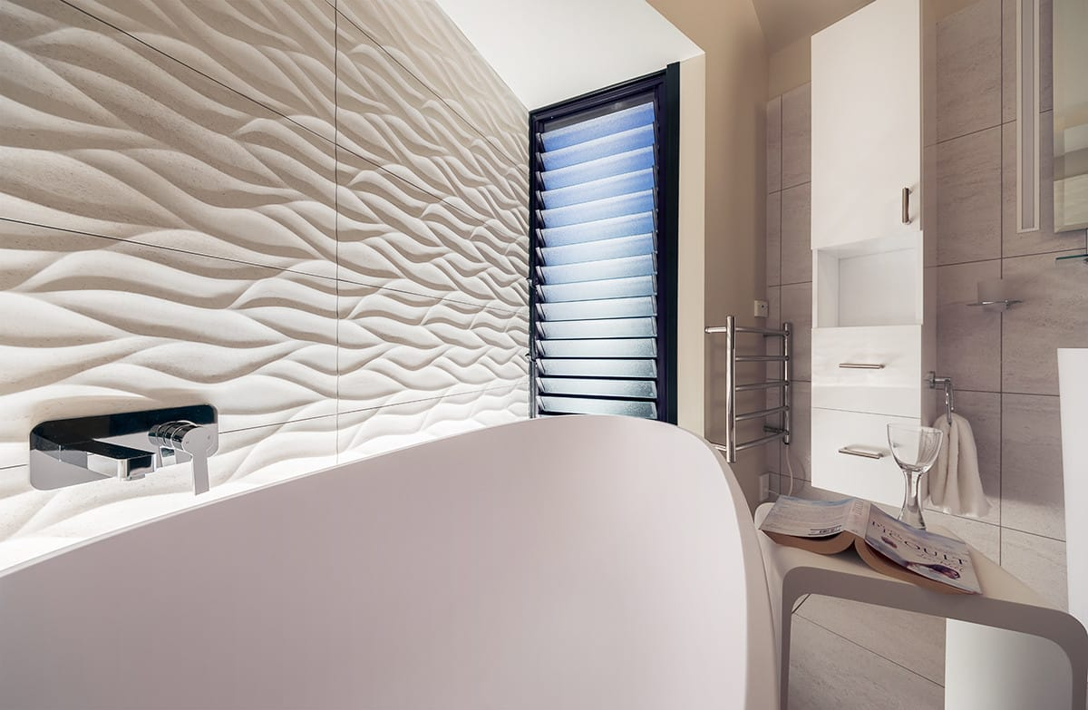 Wave-textured tiles and sandy colour scheme match home's seaside setting