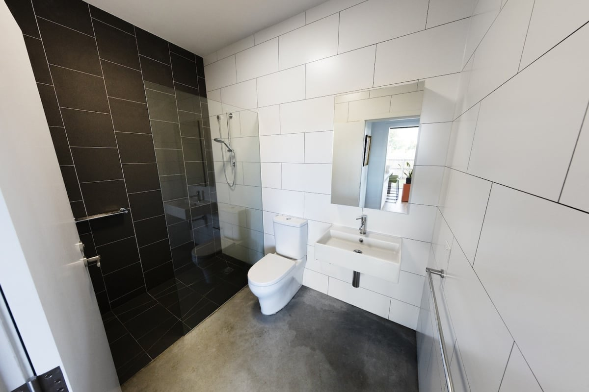This bathroom features floor to ceiling tiles in contrasting black and white