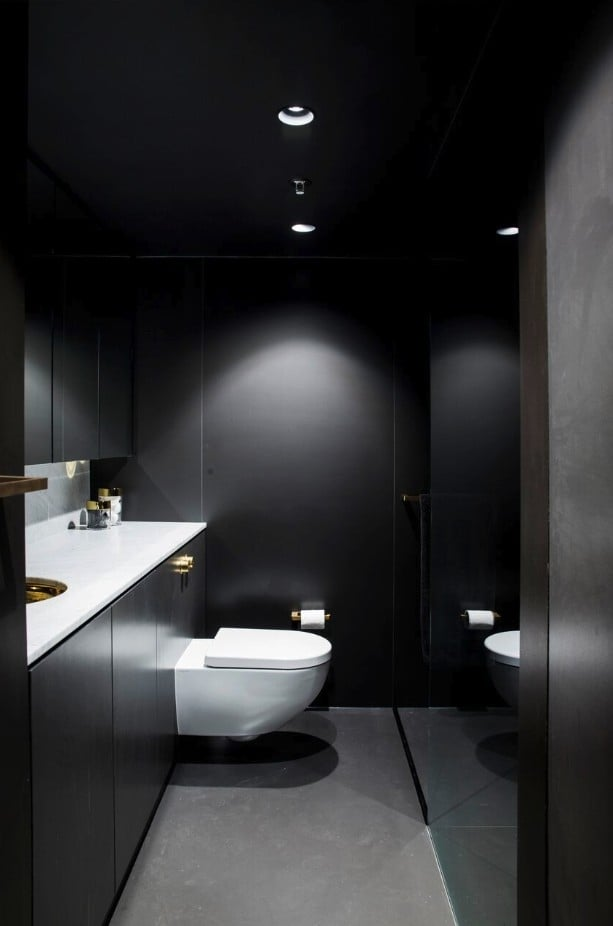 The white bathroom counter and toilet stand out amongst the gray of the walls and ceiling