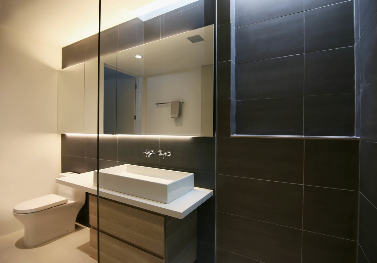 This bathroom features a wall of large back tiles to balance the white floor and ceiling