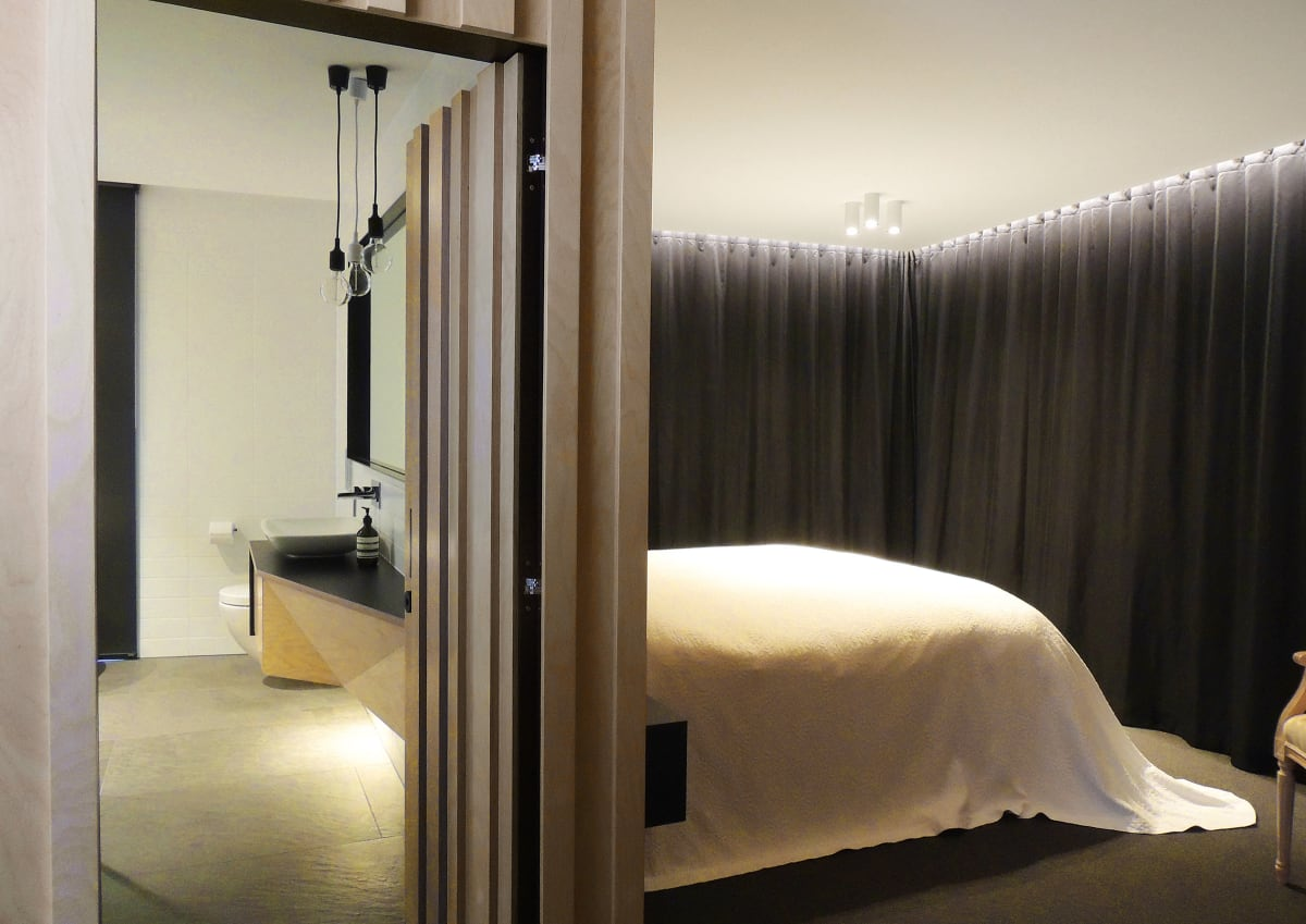 Modest-sized master suite features hand-crafted vanity, mirror and bedside tables