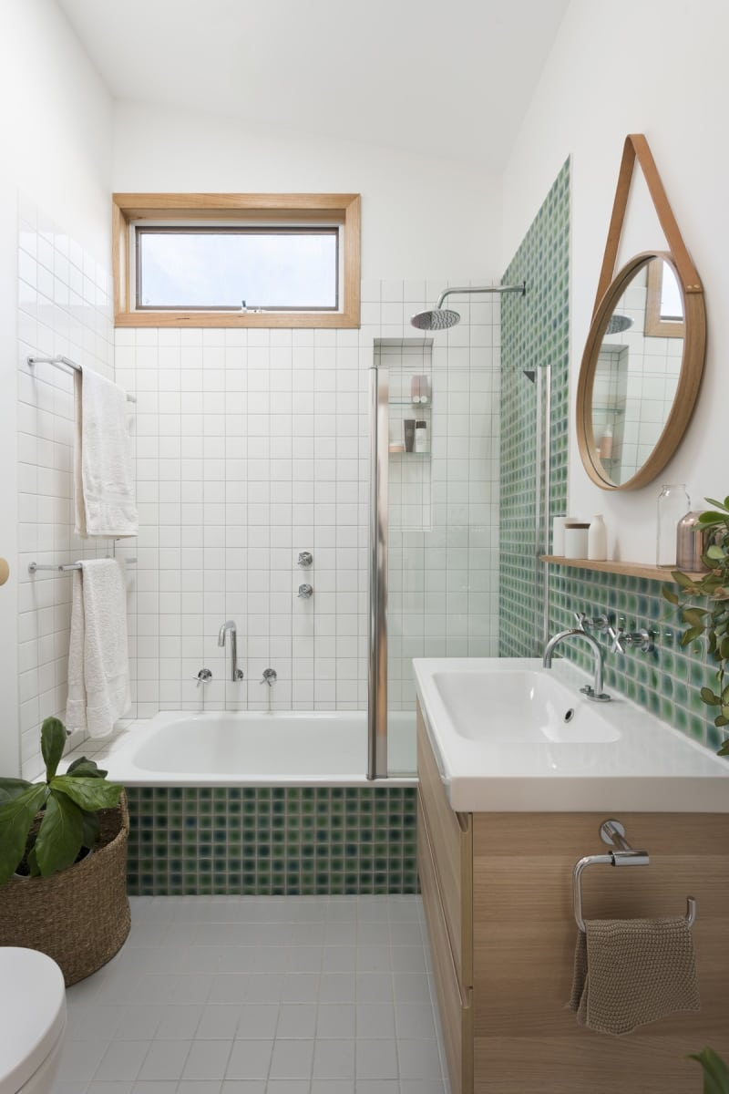 White and green tiles, wood elements and a suspended mirror make for an interesting bathroom
