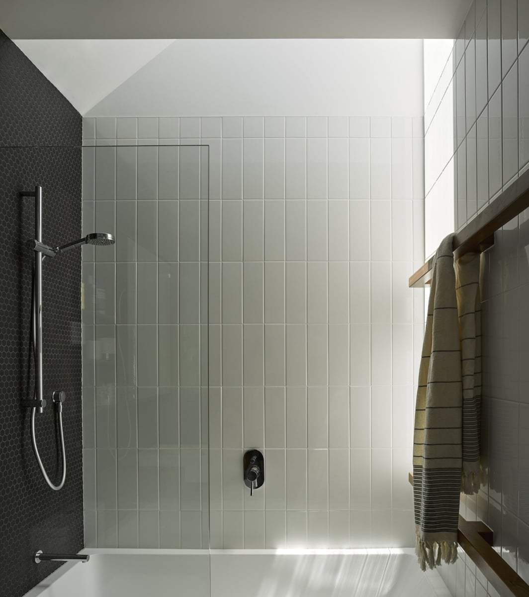 The black and white bathroom features an angled ceiling