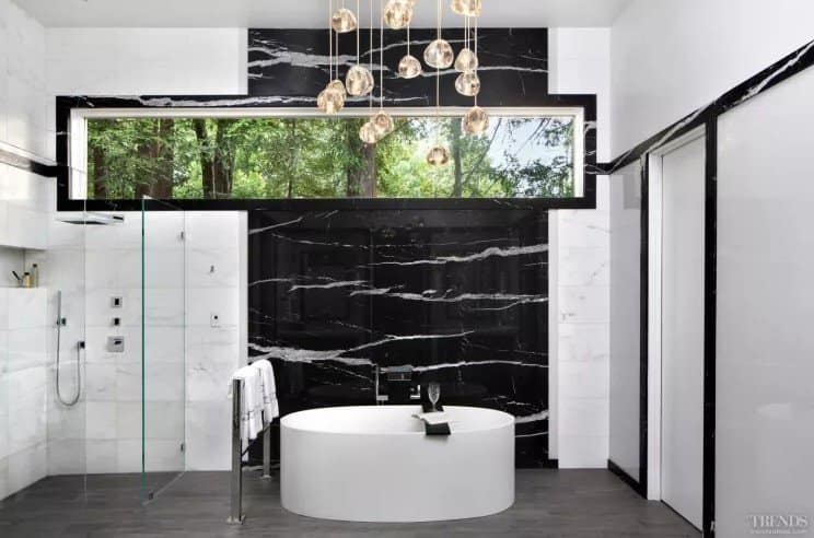 Large marble slabs in white and black and matching wall trims all help to visually reduce the ceiling height in this remodeled bathroom