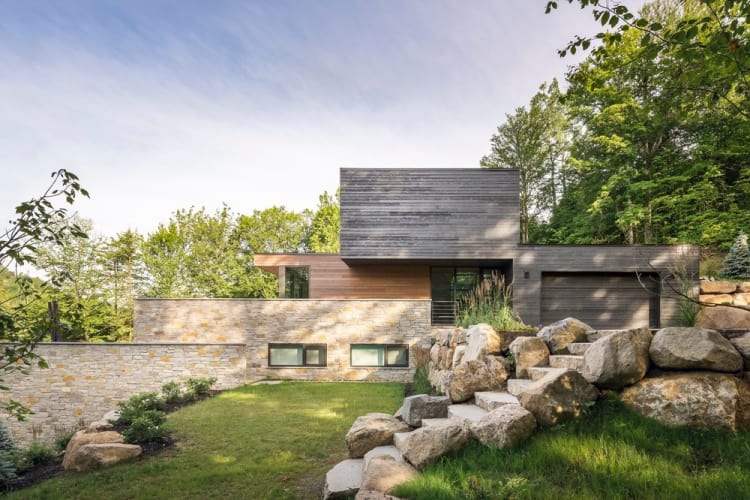 Stone walls and timber facades on the Estrade Residence merge with the rocky alpine setting