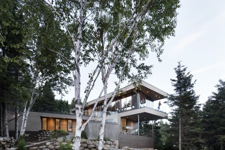 Set among trees, the house's second floor cantilevers towards the river views