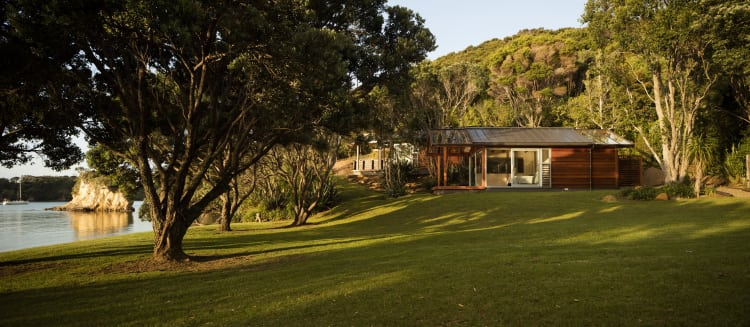 These two seaside cabins are cut into the hillside twenty meters from a small intimate beach in the Bay of Islands