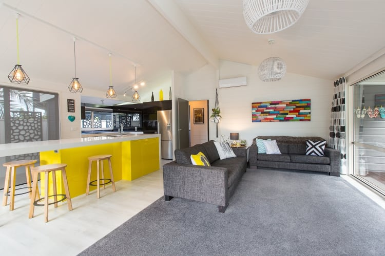 The kitchen originally included a bright green accent colour, which was then changed to yellow with grey tinted mirror as splash backs