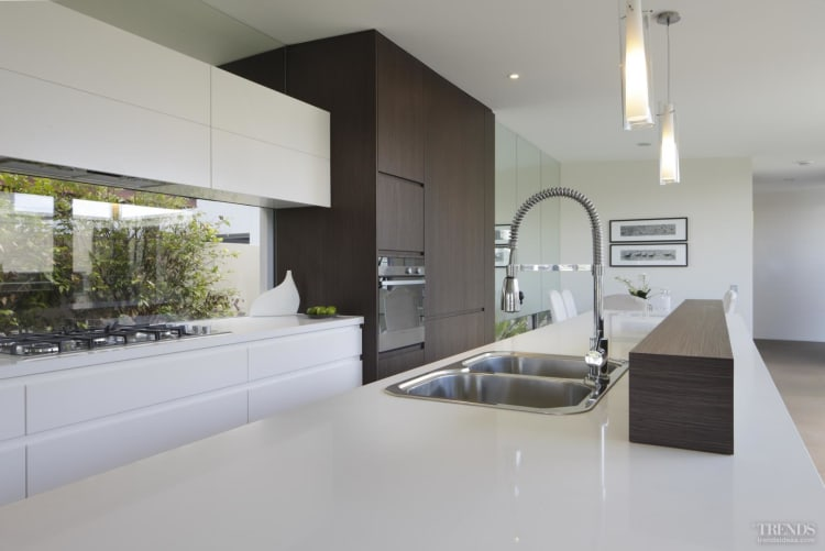 A modern family kitchen with an island, in white and timber veneer, by Ryan Designer Homes