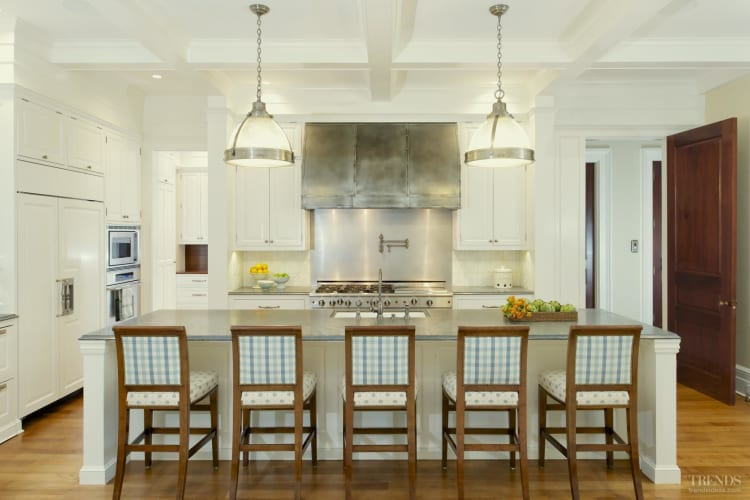 Traditional kitchen with white cabinets, integrated appliances and custom rangehood