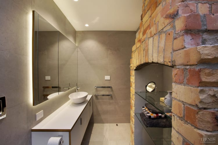 Renovated master suite with exposed brick fireplace, contemporary cabinets