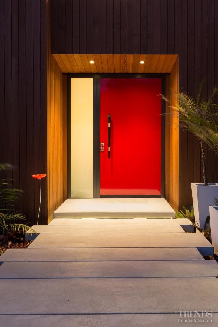 A dramatic red front door is just one of the many considered paint choices in this new home
