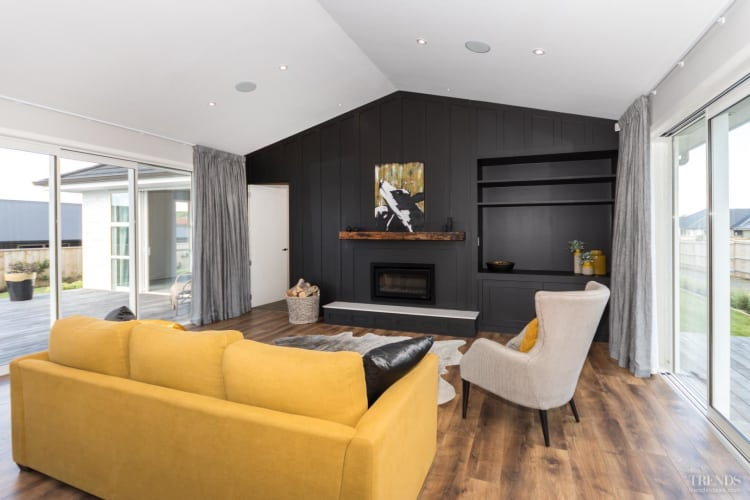 An inky black feature wall adds a dramatic touch to the light-filled living room in this Waiata showhome, by Landmark Homes