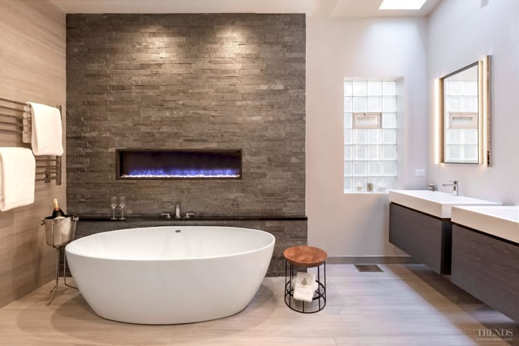 Stone-look tiles and a wall-mounted gas fire give this ensuite a welcoming feel
