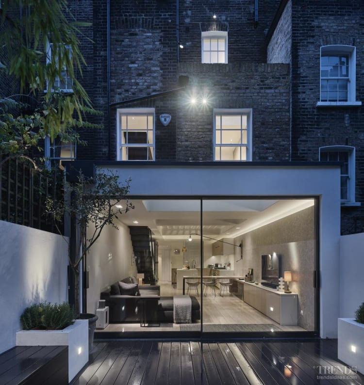 Contemporary basement-level kitchen basks in natural light thanks to a feature ceiling of glass pavement lights